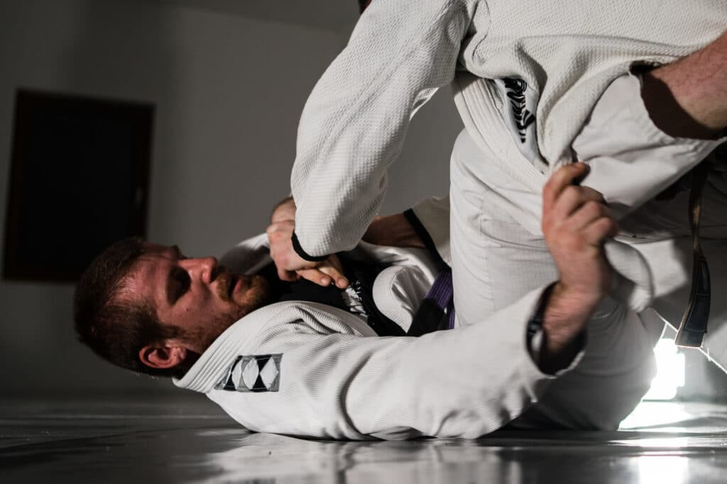 Brazilian jiu jitsu BJJ sparing in training two athletes martial arts fighters wearing gi kimonos training to fight lapel guard