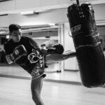 man wearing training gloves kicking heavy bag inside gym near mirror walls